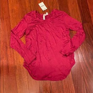 A maroon shirt with holes